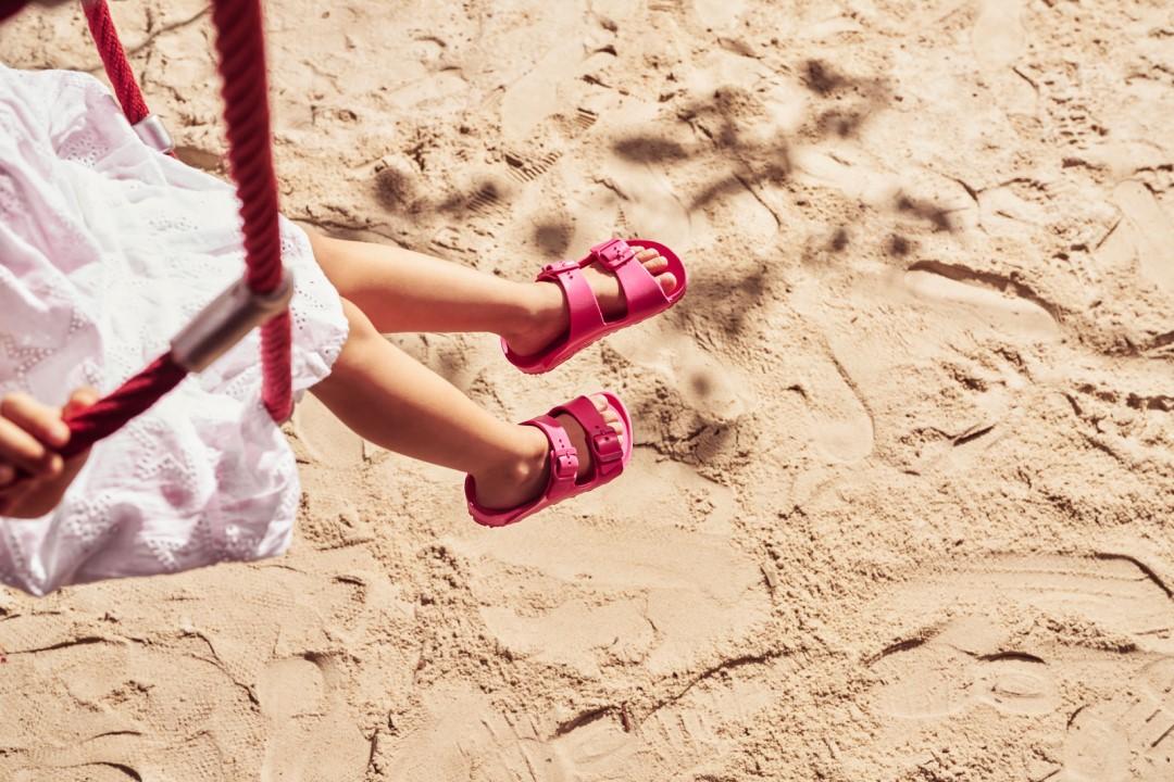 child wearing beetroot EVA birkenstock sandals at beach