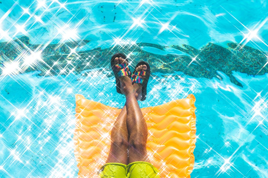 legs on a pool float over pool water wearing chaco chillos tiedye slide sandals