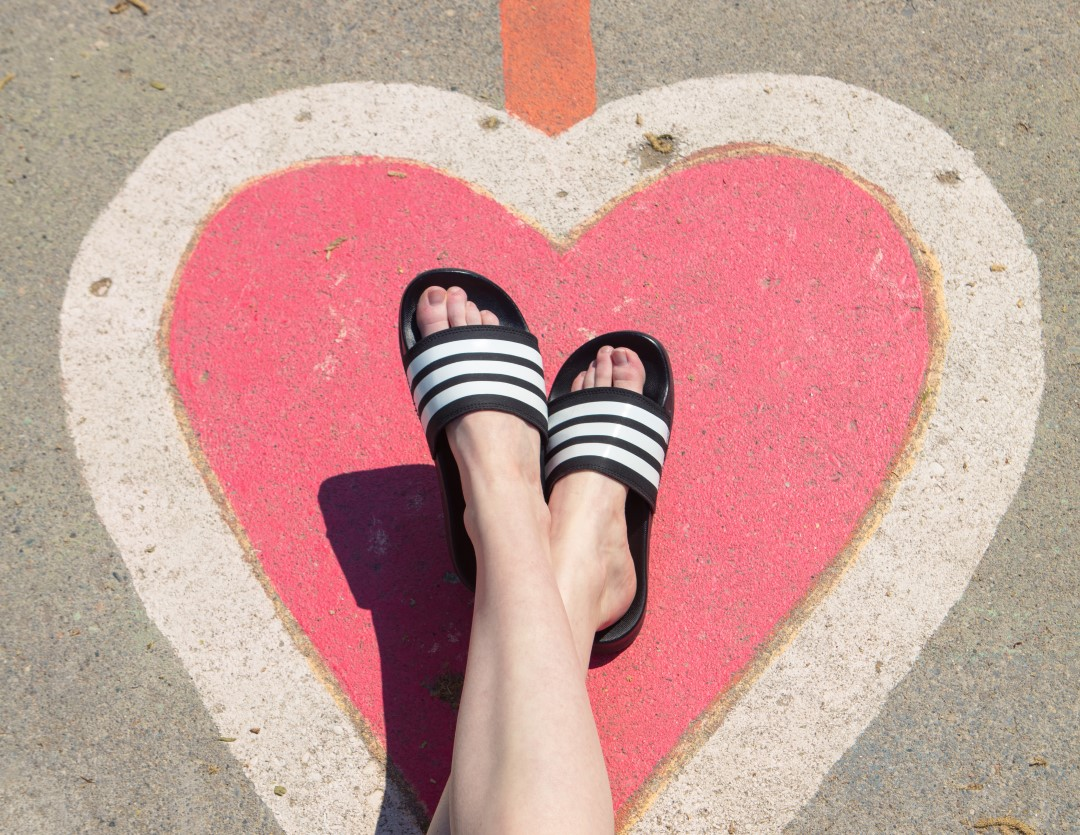 pink heart on pavement with women's legs wearing adidas slide sandals